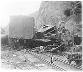 Engine smashed and on side and off track by a steep rock wall.  End of box car also off track.  Workman on side by engine<br /> D&amp;RG