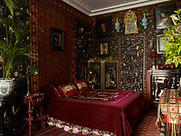 Baroque and Symbolist paintings hang on the walls of the bedroom which are covered with Chinese and Japanese silk embroidery, brocade, Arts and Crafts textiles and Renaissance Revival needlepoint panels