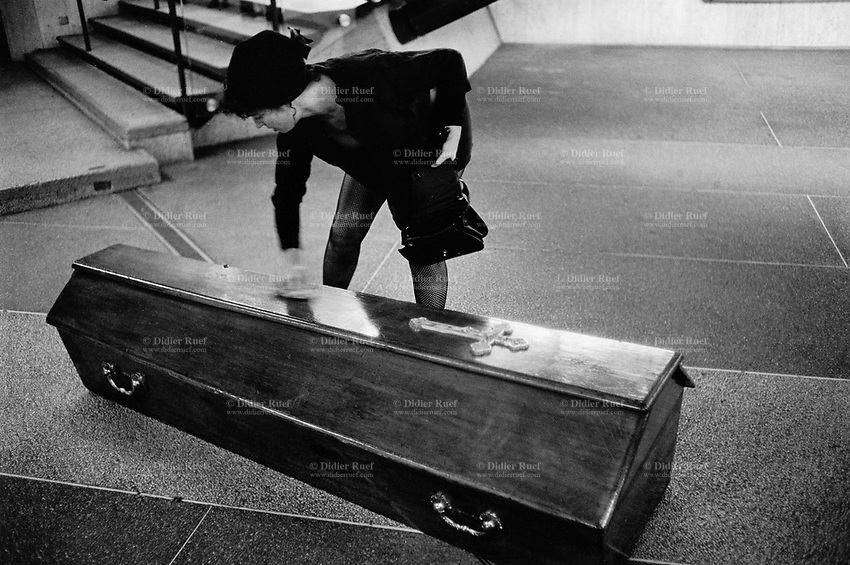 "Switzerland. Geneva. Open air theatre performance. Festival ""Bois de la Batie"". French group "" Cacahuete"". A widow, dressed in black clothes, is cleaning a coffin with a handkerchief. © 1994 Didier Ruef"