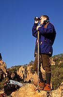 Walker using binoculars at the head of a rocky gorge. Gorges du Blavet, Provence, France.