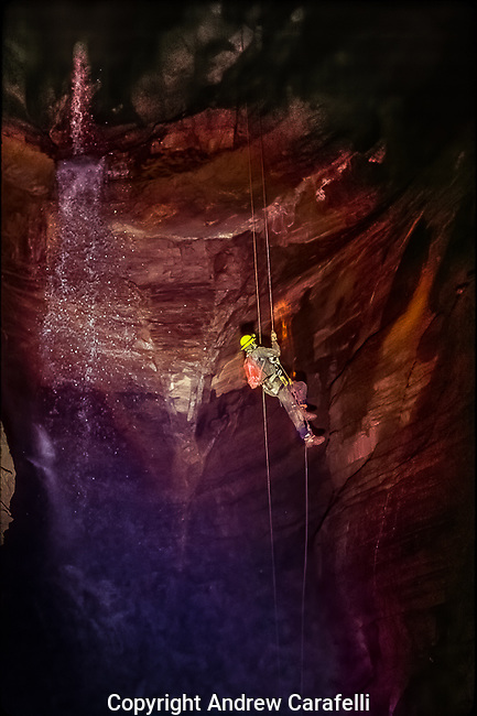 A caver ascends out of a canyon deep within Cass Cave in West Virginia, as 160 foot  Suicide Falls spills over ledges behind.