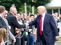 United States President Donald J. Trump shakes hands with guests as he arrives at the White House in Washington, DC following a trip from Miami, Florida on Friday, June 16, 2017.  In Miami, the President gave remarks and participated in a signing on the United States&rsquo; policy towards Cuba.<br /> Credit: Ron Sachs / CNP /MediaPunch