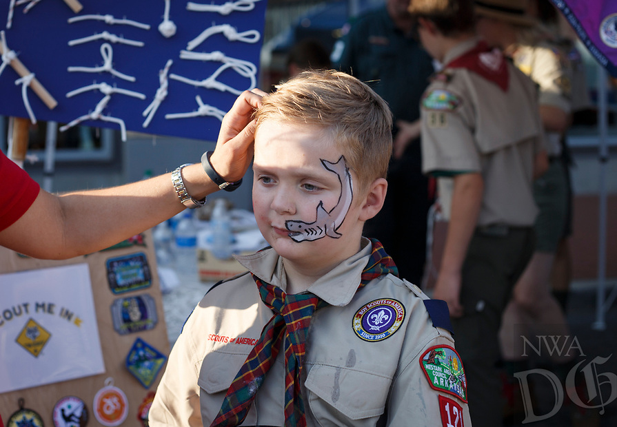NWA Democrat-Gazette/CHARLIE KAIJO Rachel Wessels of Bentonville brushes the hair of Benji Wessels, 9, of Cub Scouts pack 121 during the First Friday event, Friday, August 3, 2018 at the Bentonville Square in Bentonville.