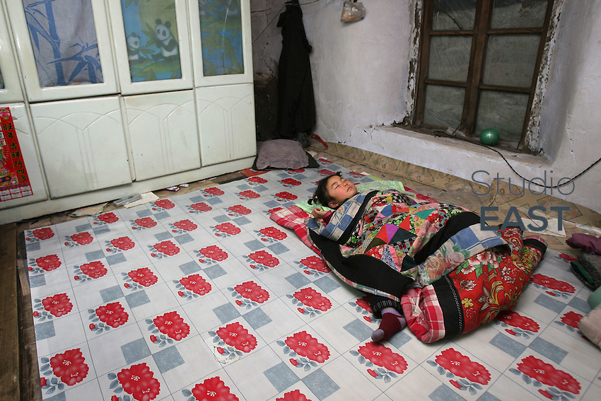 A little girl sleeps on a brick bed heated by a coal stove. That's the only heating in her two-room mud house in Yongfu, on February 27, 2006. Photo by Lucas Schifres/Pictobank