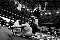 "A female Lucha libre wrestler Keira kicks down her rival Sexy Polvora during a fight at Arena Plan Sexenal in Mexico City, Mexico, 29 May 2011. Lucha libre, literally ""free fight"" in Spanish, is a unique Mexican sporting event and cultural phenomenon. Based on aerial acrobatics, rapid holds and the use of mysterious masks, Lucha libre features the wrestlers as fictional characters (Good vs. Evil). Women wrestlers, known as luchadoras, often wear bright shiny leotards, black pantyhose or other provocative costumes. Given the popularity of Lucha libre in Mexico, many wrestlers have reached the cult status, showing up in movies or TV shows. However, almost all female fighters are amateur part-time wrestlers or housewives. Passing through the dirty remote areas in the peripheries, listening to the obscene screams from the mainly male audience, these no-name luchadoras fight straight on the street and charge about 10 US dollars for a show. Still, most of the young luchadoras train hard and wrestle virtually anywhere dreaming to escape from the poverty and to become a star worshipped by the modern Mexican society."