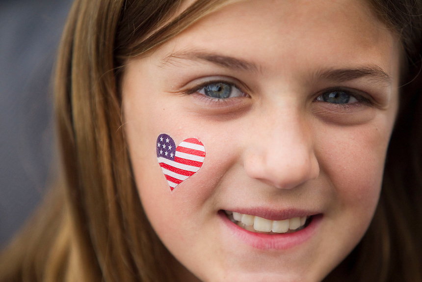 Ten year old Kennadi Jones, wears an American flag on her cheek as she takes part in the Fourth of July Parade through the town of Ridgefield Monday July 4, 2016. (Photo by Natalie Behring/ for the The Columbian)
