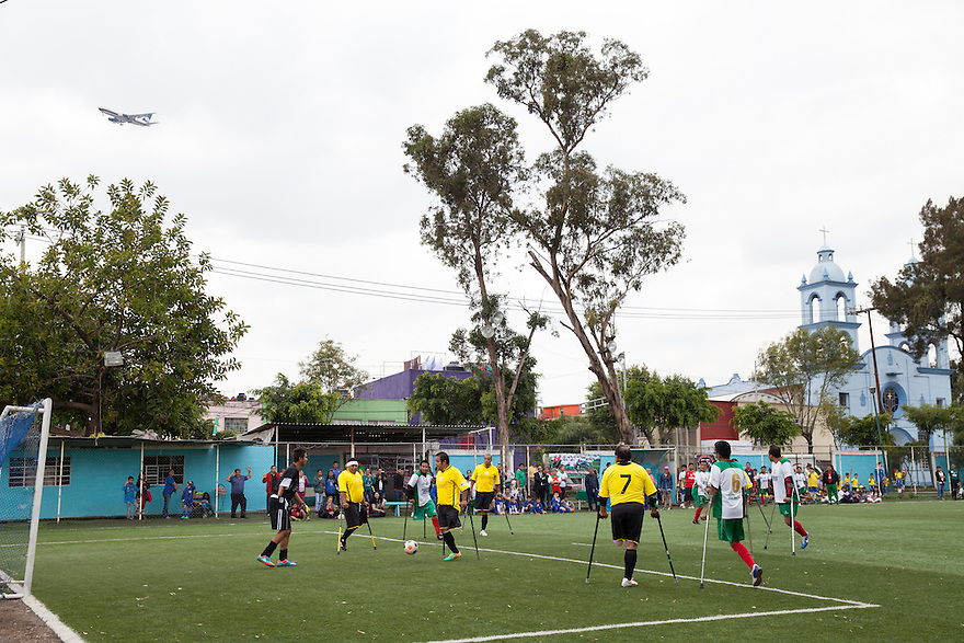 "Players from Guerreros Aztecas during a soccer game with Los Dragones (""the Dragons"") in Mexico City, Mexico on July 5, 2014. Guerreros Aztecas (""Aztec Warriors"") is Mexico City's first amputee football team. Founded in July 2013 by five volunteers, they now have 23 players, seven of them have made the national team's shortlist to represent Mexico at this year's Amputee Soccer World Cup in Sinaloa this December. The team trains twice a week for weekend games with other teams. No prostheses are used, so field players missing a lower extremity can only play using crutches. Those missing an upper extremity play as goalkeepers. The teams play six per side with unlimited substitutions. Each half lasts 25 minutes. The causes of the amputations range from accidents to medical interventions – none of which have stopped the Guerreros Aztecas from continuing to play. The players' age, backgrounds and professions cover the full sweep of Mexican society, and they are united by the will to keep their heads held high in a country where discrimination against the disabled remains widespread. (Photo by Bénédicte Desrus)"