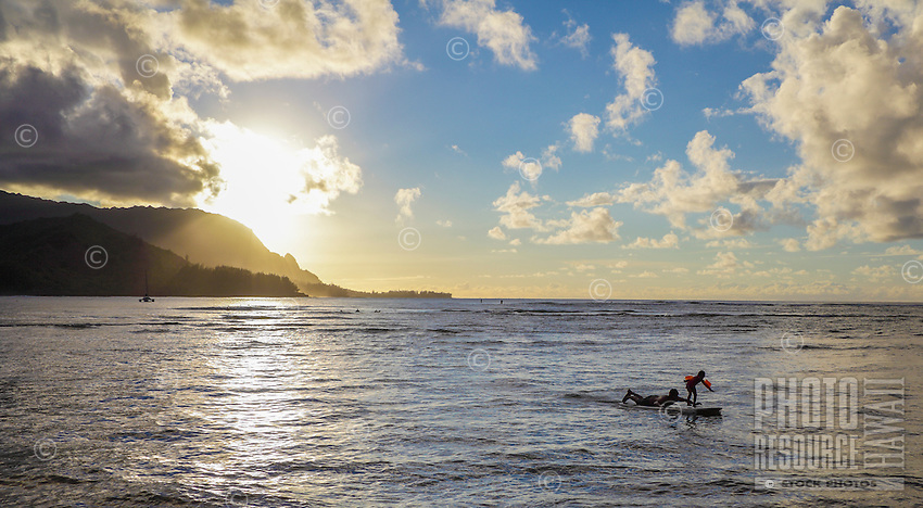 A young girl wearing floaties stands on her father's surfboard at sunset, with standup paddlers and surfers in the distance, Hanalei Bay, Kaua'i.