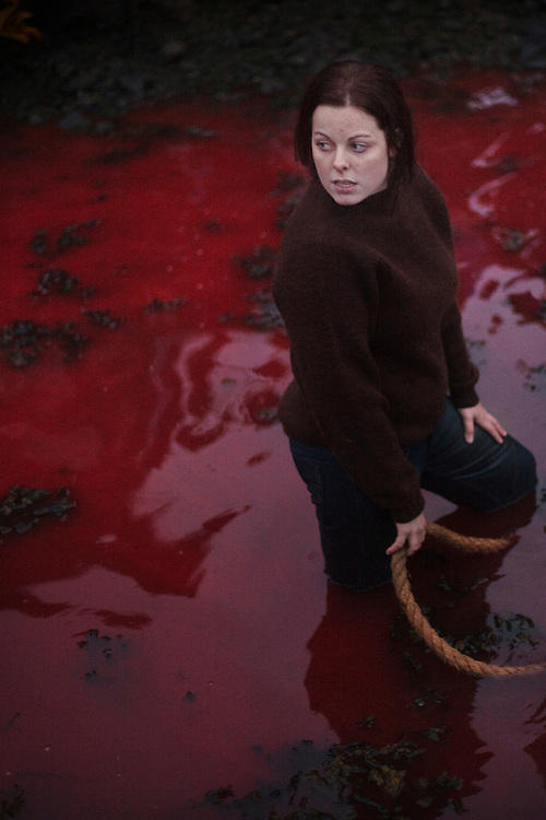 A woman holds the end a rope after helping to pull a pilot whale on shore on July 18, 2010.  Men, women and young people all take part in the kill.
