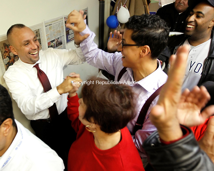"""Waterbury, CT-06 November 2012-110612CM12-  Victor Cuevas, left, Democratic candidate for the 75th District  celebrates with BJ Rodriguez, Team Leader for the 75th District Democratic Town Committee, right, and Dolly Rosario, of Waterbury below, after at his headquarters Tuesday night in Waterbury.  Cuevas  defeated Republican John """"Jack"""" Alseph Jr.     Christopher Massa Republican-American"""