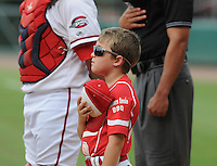 A youth baseball player stands for the National Anthem prior to a game between the Greenville Drive and Lakewood BlueClaws on July 13, 2011, at Fluor Field at the West End in Greenville, South Carolina. (Tom Priddy/Four Seam Images)