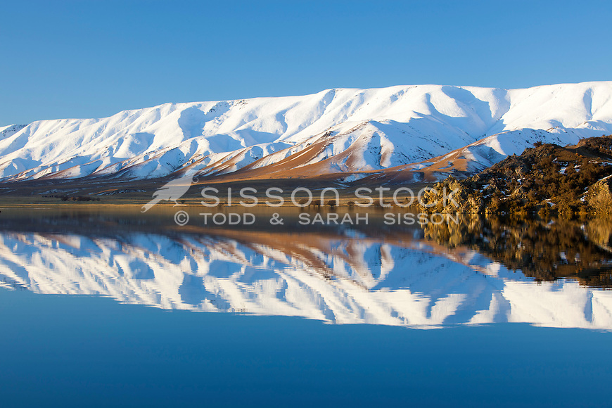 Snow covered Hawdun Ranges reflection in Falls Dam, near St Bathans, Central Otago, New Zealand