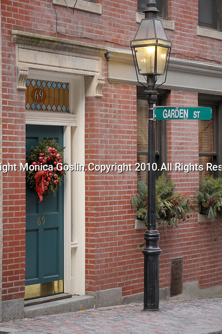 A brick building with a teal door and a holiday wreath on Garden Street in Beacon Hill in Boston, MA.