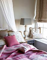 A bed richly dressed with patterned cushions and a striped bed cover dominates this small bedroom