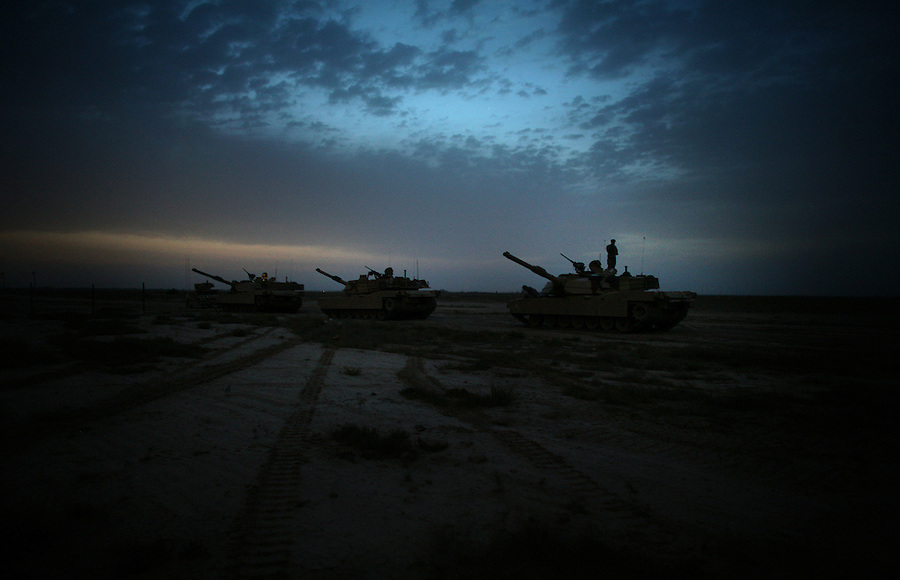 A trio of tanks and their crews wait for a mission in the desert on the outskirts of Baqubah, Iraq on Sunday May 27, 2007.