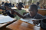 Children in Jean-Rabel in northwestern Haiti study in a temporary classroom while work continues on reconstructing an elementary school that was heavily damaged during Hurricane Matthew in 2016. Church World Service, a member of the ACT Alliance, is helping the community repair the school.