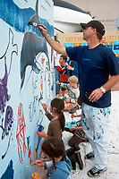 The artist Wyland with children, painting a mural at the Birch Aquarium of the Scripps Institute of Oceanography, San Diego, California