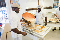 People watch as Daniel Ferguson, 50, (from left), Maurice Scott, 28, and Davian Miller, 24,  make fudge at Murdick's Fudge in Edgartown, Martha's Vineyard, Massachusetts, USA. Ferguson is from Jamaica and has an H2B seasonal foreign worker visa. He says 2017 is his sixth summer season working in the fudge shop. During off-months, he returns to Jamaica where he can be with family and escape the cold weather. Miller has worked here for two seasons, and Scott for four seasons. Most of the shop's workers are seasonal foreign workers. Other companies on Martha's Vineyard and around the US had difficulty obtaining H2B visas, but Murdick's Fudge received all it requested.