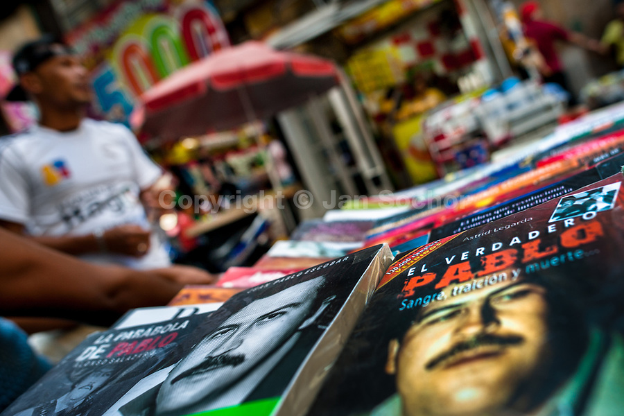 """Paperback books, depicting the drug lord Pablo Escobar on their covers, are seen arranged at the market stand on the street in Medellín, Colombia, 7 December 2017. Twenty five years after Pablo Escobar's death, the legacy of the Medellín Cartel leader is alive and flourishing. Although many Colombians who lived through the decades of drug wars, assassinations, kidnappings, reject Pablo Escobar's cult and his celebrity status, there is a significant number of Colombians who admire him, worshipping the questionable """"Robin Hood"""" image he had. Moreover, in the recent years, the popular """"Narcos"""" TV series has inspired thousands of tourists to visit Medellín, creating a booming business for many but causing a controversial rise of narco-tourism."""