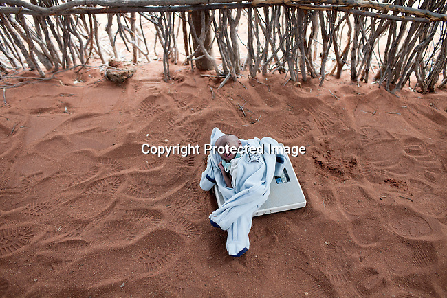 MATHAHALIBAH, KENYA - JULY 4: Umi Adan Olow, 3 months old, is weighed by Daniel Wanyoike, a community therapeutic nurse for Save the Children on July 4, 2011 in Mathahalibah, Kenya. The child weighed 1,7 kilograms. The team examined about thirty children, among them some severely malnourished. Umis's mother brought her to the outreach site. The child has been sick a lot since birth. Amina Yare Isak, her mother, has two other children in the Save the Children nutrition program. The mother blames the drought for her children's sickness. Her livestock was finished and the lack of milk made her children malnourished. Two successive poor rains, entrenched poverty and lack of investment in affected areas have pushed millions of people into a fight for survival in the Horn of Africa. This is the driest this area have been since sixty years. (Photo by Per-Anders Pettersson)