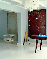 Adjoining rooms unified by a white gloss floor with a small pool table