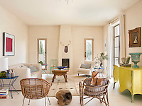 Light floods into the living area from large French windows and a pair of tall narrow windows either side of the fireplace