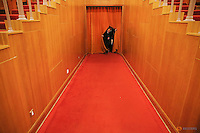 A delegate walks out of a curtain at the Great Hall of the People during the second plenary session of the NPC in Beijing, China, March 9, 2016.