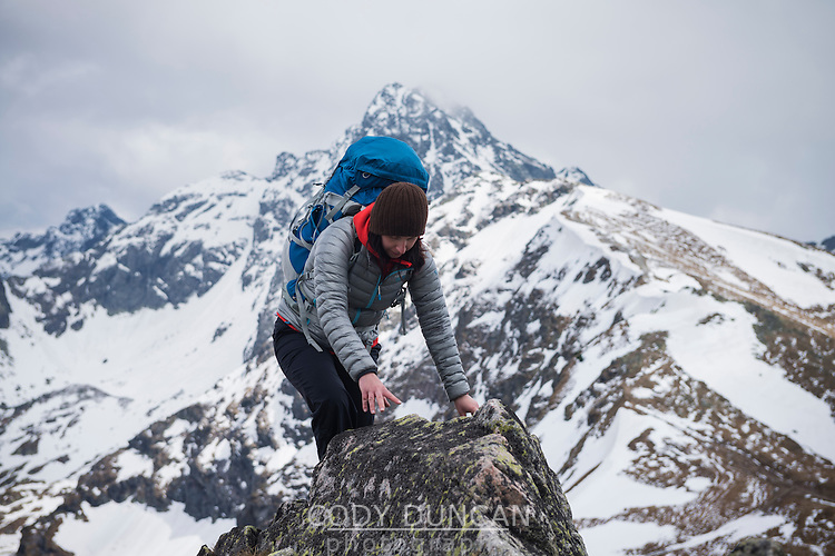 Female hiker scrambles over rock in Tatra mountains, Poland