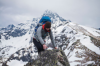 Female hiker scrambles over rock in Tatra mountains, Poland