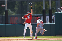 Northeastern Huskies first baseman Jake Farrell (18) stretches for the throw as J.T. Jarrett (42) of the North Carolina State Wolfpack hustles down the line at Doak Field at Dail Park on June 2, 2018 in Raleigh, North Carolina. The Wolfpack defeated the Huskies 9-2. (Brian Westerholt/Four Seam Images)