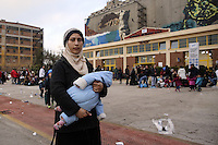 Pictured: A young mother clutching her baby walks alone as dozens of other migrants rest on the ground after disembarking at the port of Piraeus Friday 26 February 2016<br /> Re: Hundreds of refugees that crossed the border from Turkey to the Greek islands, have arrived at the port of Piraeus near Athens, Greece
