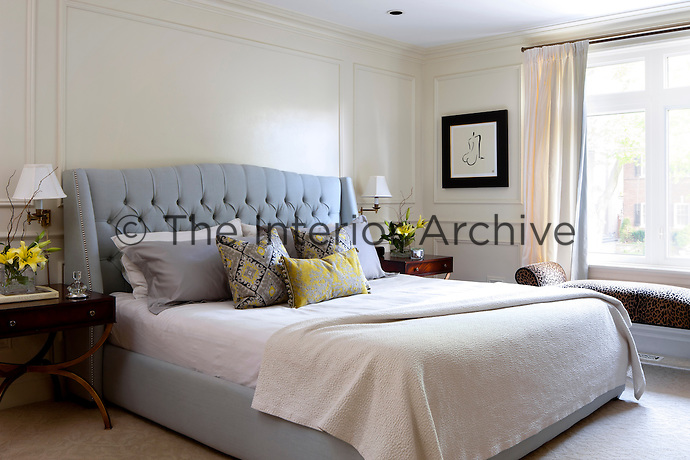 A luxurious master bedroom. Cool grey and yellow tones give the room a calm, restful ambiance.