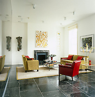 The floor of the living room has been laid with tiles of Indonesian sandstone and the red leather armchair is a prototype designed by the architect's father Herbert Selldorf