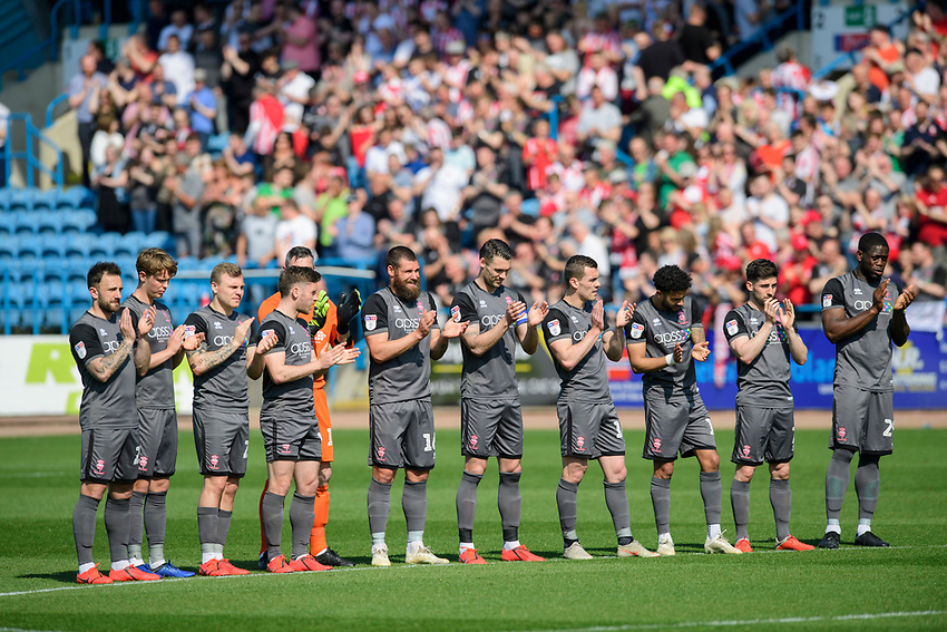 Lincoln City players during a minutes applause, in memory of Ivor Broadis<br /> <br /> Photographer Chris Vaughan/CameraSport<br /> <br /> The EFL Sky Bet League Two - Carlisle United v Lincoln City - Friday 19th April 2019 - Brunton Park - Carlisle<br /> <br /> World Copyright © 2019 CameraSport. All rights reserved. 43 Linden Ave. Countesthorpe. Leicester. England. LE8 5PG - Tel: +44 (0) 116 277 4147 - admin@camerasport.com - www.camerasport.com