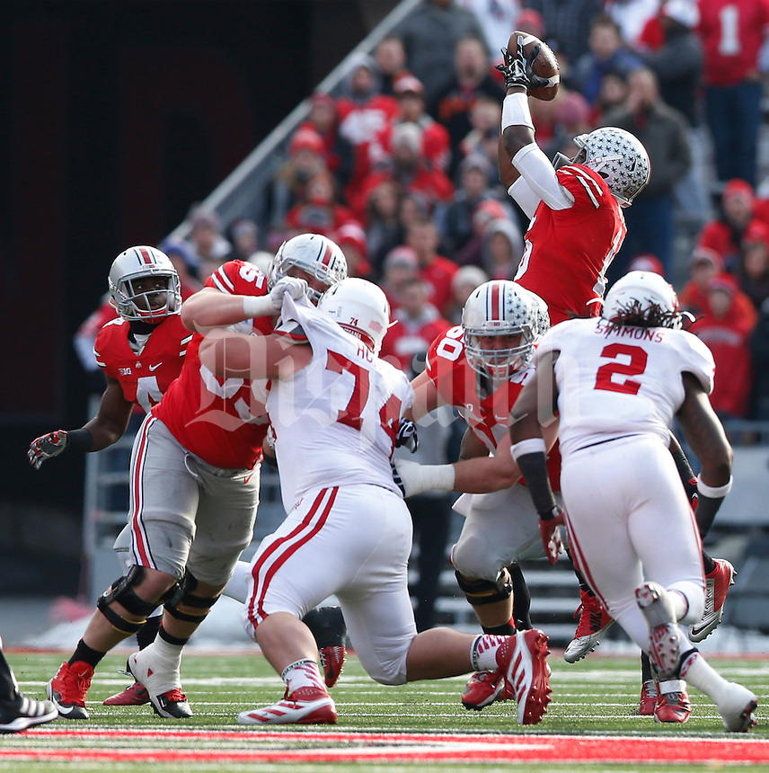 Ohio State Buckeyes quarterback J.T. Barrett (16) brings in high snap in the third  quarter at Ohio Stadium Nov. 22, 2014.(Dispatch photo by Eric Albrecht)
