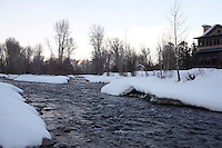 The icy waters of the Big Wood river flow past the snow-covered banks at the end of the garden