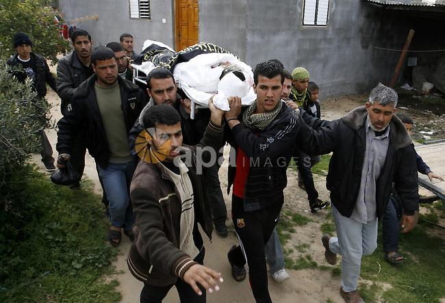 Palestinian mourners carry the body of Raafat Abu Eid , 24-years-old, a member of the Islamic Jihad's armed wing, the Al-Quds Brigades, during his funeral in Khan Yunis in the southern Gaza Strip, on March 12, 2012. Eid and fellow militant Hamada Suleiman Abu Mutlaq were both killed in one of eight overnight Israeli air strikes bringing the death toll of Palestinians to 21 as the bloodshed entered its fourth day. Photo by Abed Rahim Khatib