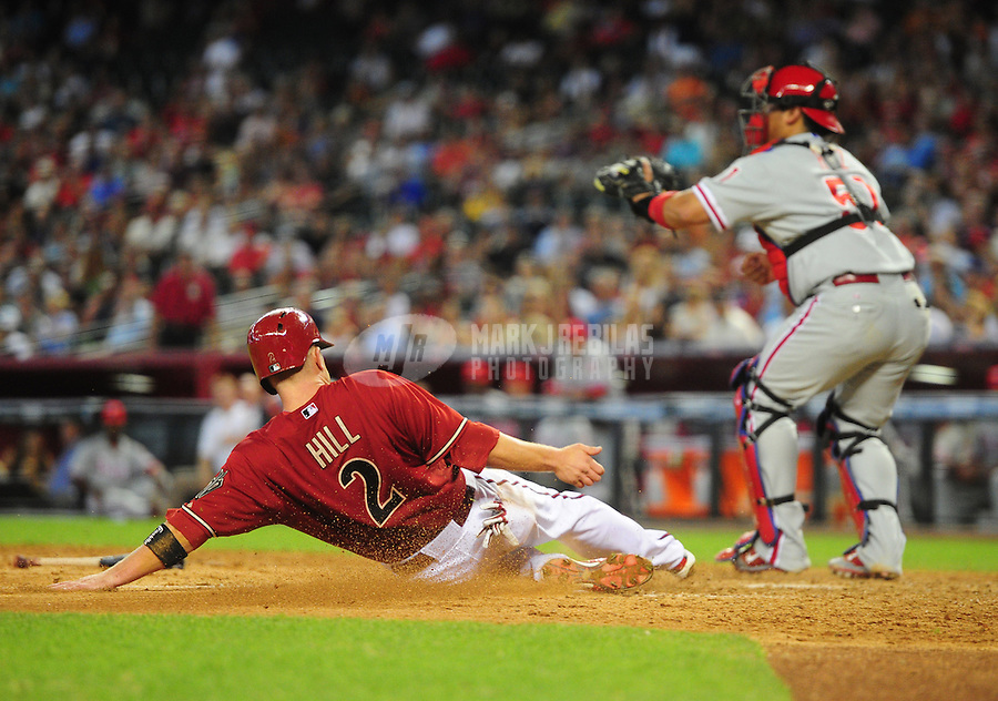 Apr. 25, 2012; Phoenix, AZ, USA; Arizona Diamondbacks base runner (2) Aaron Hill slides home to score ahead of the ball to Philadelphia Phillies catcher Carlos Ruiz in the seventh inning at Chase Field. Mandatory Credit: Mark J. Rebilas-