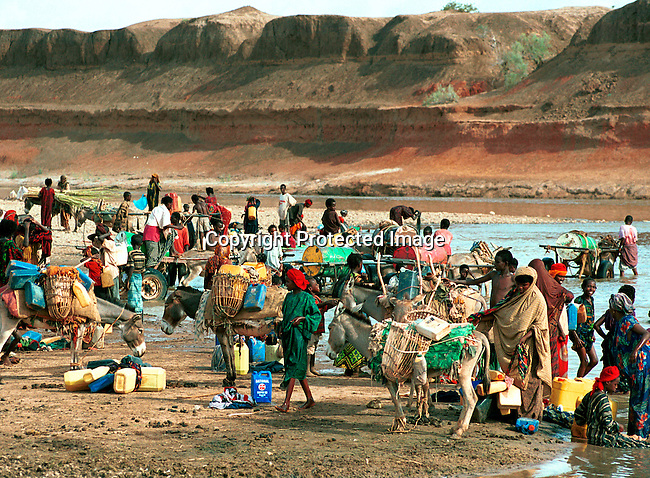 dicoeth00009 Ethiopia..People fetching water on April 13, 2000 in a river close to Gode in Ogaden province in  Ethiopia. The area is extremly hot and drought stricken most of the year. Thousands of people came to Gode looking for food and water in the spring of 2000. .©Per-Anders Pettersson/iAfrika Photos