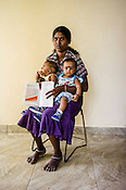 A Sri Lankan woman poses for a photo with her children and the CHDR- Child Health Development Record Card (immunization/vaccination card) in the Ministry of Health office in Tharmapuram Village in Kilonochchi, Sri Lanka.  Photo: Sanjit Das/Panos