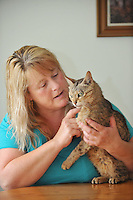 Pictured: Lisa Darney from with ' Saffie' her cat which went missing for 8 years.<br /> Re: A family has been reunited with their cat eight years after she went missing.<br /> Saffie went missing from her home in Sandfields in Port Talbot in 2008 while her owner, Lisa Darney was away on holiday.<br /> The 44-year-old searched for years for Saffie, but was never able to find her and had begun to give up hoping that they would be reunited.<br /> But, earlier this week, Lisa received a phone call from a couple in Nant Y Moel in Bridgend who had found Saffie at their allotment.<br /> Now, Saffie has been reunited with her family.<br /> &quot;We got Saffie in 2005 as a Christmas present. She was only two months old at the time, and we absolutely adored her,&quot; Lisa said.<br /> &quot;I went away on holiday in September 2008 and I left my son to look after the animals, but she got out of the house and over the fence. We were devastated.
