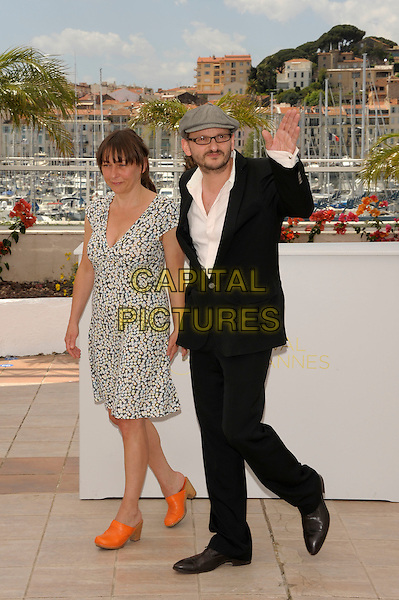 Steffi Kuhnert,  Milan Peschel.'Half auf Freier Strecke' photocall.64th International Cannes Film Festival, France.May 2011.full length pint dress orange shoes black suit cap hat glasses hand waving  .CAP/PL.©Phil Loftus/Capital Pictures.