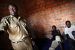 As well as training officers, OHCHR staff monitor camp conditions, treatment of prisoners and observance of due process. Here the Officer in Charge of the Police Post escorts OHCHR staff to interview three men recently arrested in the camp.<br /> <br /> During the 20-year civil war in Northern Uganda, well over a million people have been forced from their homes into camps. Fleeing the horrific abuses that have characterised this conflict - including widespread killing, rape, torture and mutilation - they have exchanged a peaceful existence as subsistence farmers for a life of destitution and dust. This is just one one those camps. Located in Amuru district, it is home to some 40,000 men, women and children. The war has reached an uneasy peace, but many people still do not dare to go home, even though they have been waiting for two decades. And in a country with an average life expectancy of just 47 years, that's a long time to wait.<br /> <br /> While they do, the United Nations Office of the High Commissioner for Human Rights (OHCHR) is working to ensure that they can live in safety and dignity. This means the Office monitors human rights abuses, trains the police who manage the camps, and makes sure that the people here know their entitlements and where they can go for help when they need it.