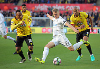 Stephen Kingsley of Swansea City (C) crosses the ball while being marked by Juan Zuniga (L) and Younes Kaboul of Watford (R) during the Premier League match between Swansea City and Watford at The Liberty Stadium on October 22, 2016 in Swansea, Wales, UK.