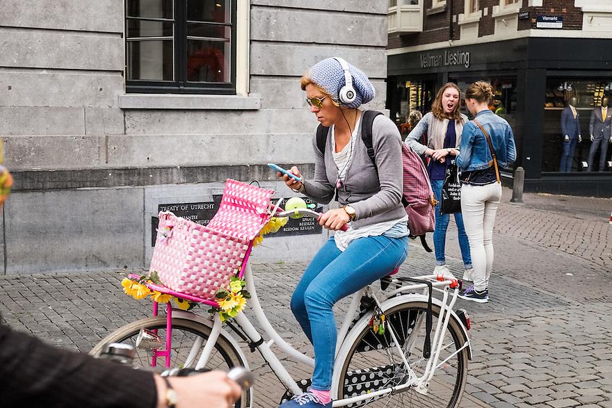 Nederland, Utrecht, 16 juni 2015 <br /> Meisje met mooie fiets en koptelefoon op haar hoofd, rijdt door de stad terwijl ze ook met haar telefoon bezig is. Ze is helemaal in haar eigen wereldje verzonken. <br /> <br />  Foto: Michiel Wijnbergh