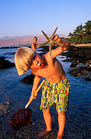 Boy playing in the tide pools finding a star fish on the Big Island