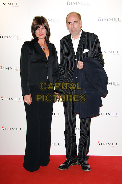 Miranda Davis & Mick Jones.The Rimmel London party, Battersea Power Station, London, England..September 15th, 2011.full length black suit dress married husband wife pinstripe.CAP/CJ.©Chris Joseph/Capital Pictures.