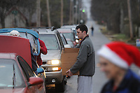 NWA Media/ J.T. Wampler - Volunteers load food boxes into cars Wednesday Dec. 24, 2014 in Bentonville. The Bentonville Kiwanis  Club distributed 540 boxes of food to area families Wednesday.