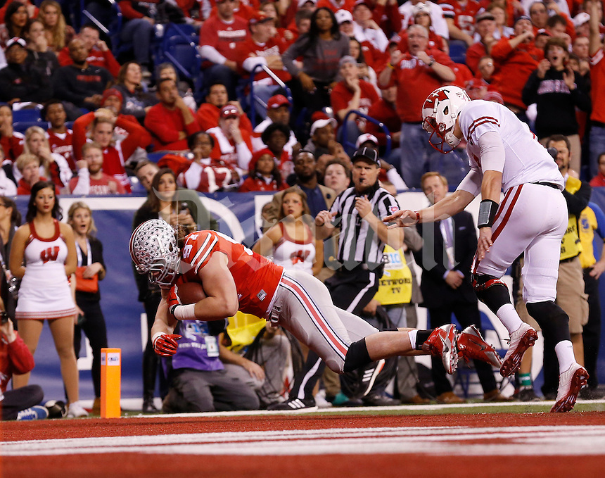 Ohio State Buckeyes defensive lineman Joey Bosa (97) dives into the endzone past Wisconsin Badgers quarterback Joel Stave (2) to score a touchdown on a fumble recovery during the second quarter of the Big Ten Championship game at Lucas Oil Stadium in Indianapolis on Dec. 6, 2014. (Adam Cairns / The Columbus Dispatch)