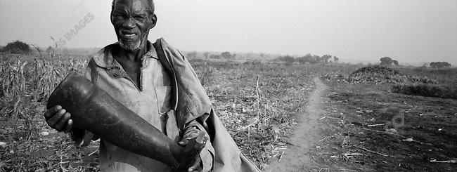 Soza holds a prosthesis he carved from a tree-trunk for his wife, Chamaze?, after she blew up on a mine. Caia District, Sofala Province, Mozambique. November, 2001.